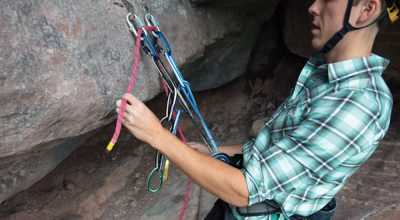 A climber threading his rope through the anchors of a sport climb in preparation for lowering..
