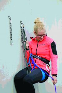 STEP 1: When you arrive at the anchor, stay on belay and clip in with a PAS, or a sling or quickdraw. In our example we show the leader clipped to one anchor bolt— her lead rope is still clipped through the bolts below her, backing up the anchor, and she remains on belay.