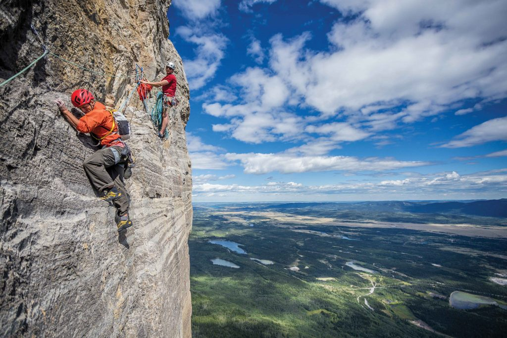 Patrick Lindsay holds the rope for Tim Banfield on one of many traverse pitches of Forbidden Corner (5.9), Mt. Yamnuska, Alberta, Canada. Photo: John Price.