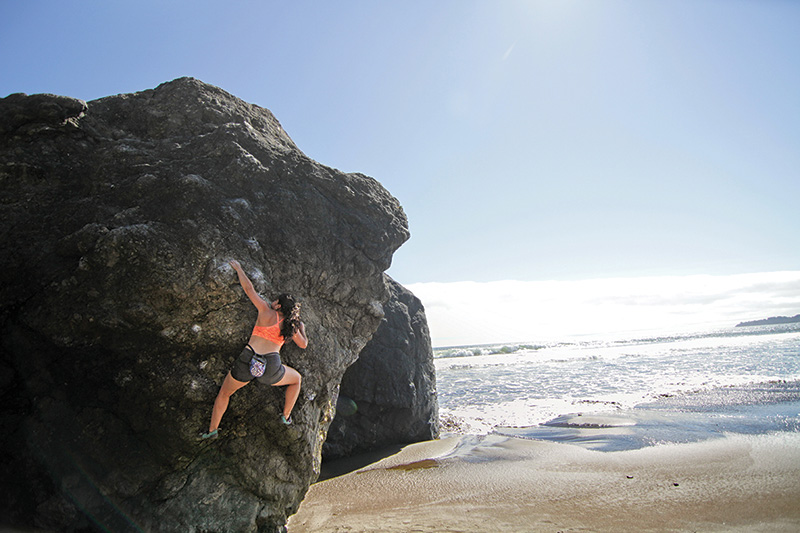 Maricela Rosales bouldering at Mickey's Beach, Bay Area, California.