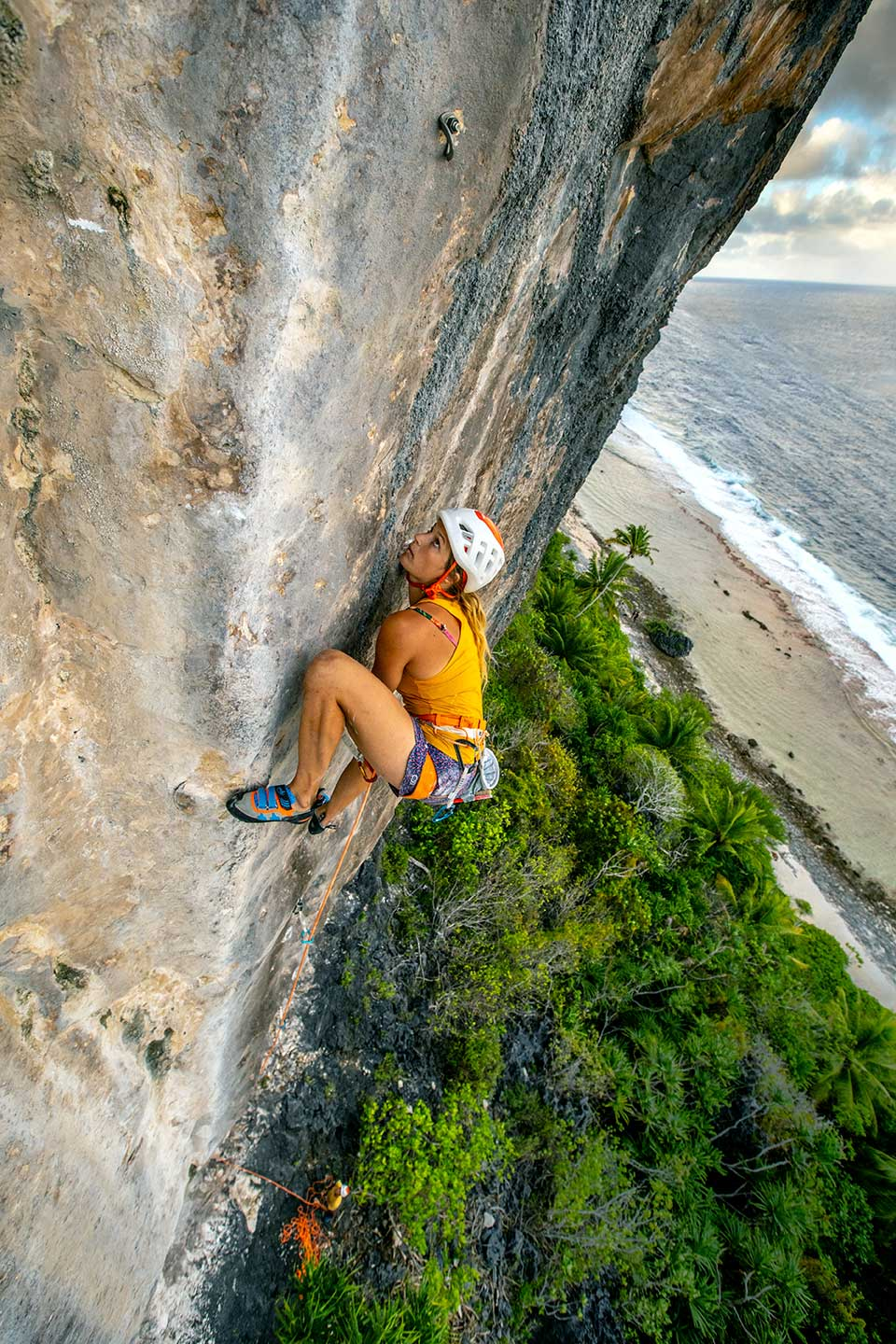 Charlotte Durif climbing a route on the coastal cliffs of Makatea.