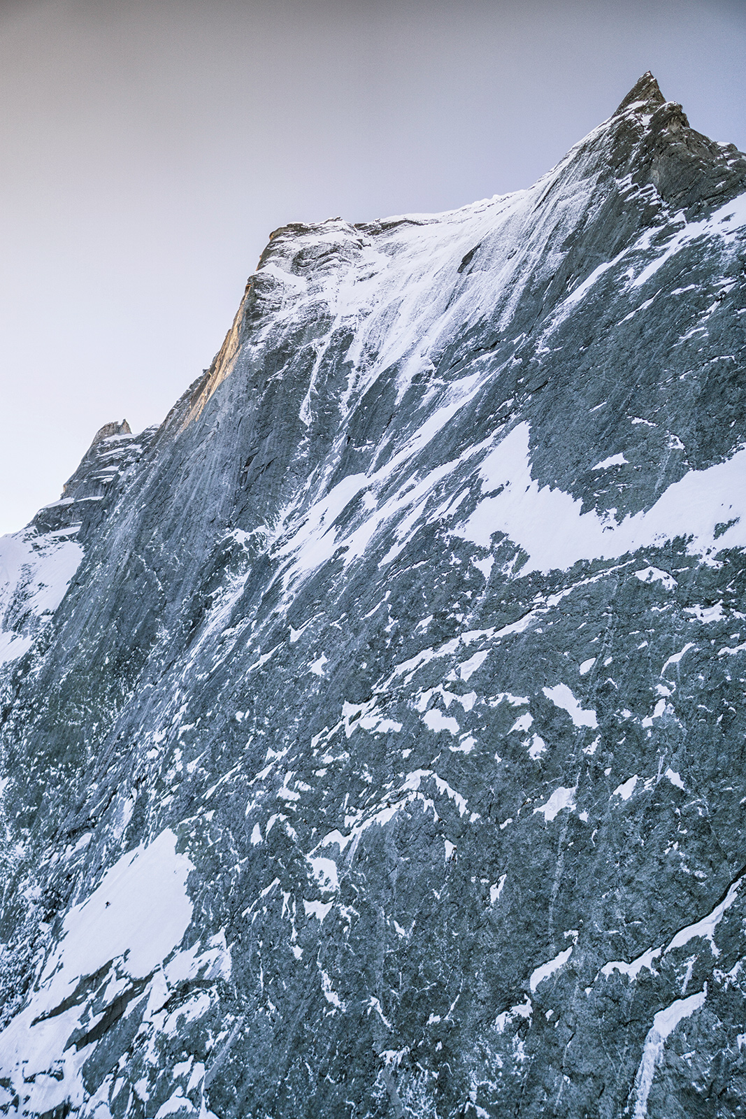 Ballard, on the snowfield in the lower left of the photo, races up the North Face of the Piz Badile. He climbed the 2,750-foot Cassin Route in one and a half days, encountering sections as difficult as M7. Ballard said the Piz Badile was the hardest of the classic North Faces. Photo: Ruggero Arena.