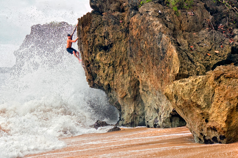 Chris Sierzant battles waves while exploring the untapped beach bouldering in Manati.