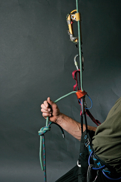 <strong>1.</strong> Transfer weight. Rappel until your brake hand almost touches the knot. Shove your ascender up the rope, letting it engage and take all of your weight. Stopping with your rap device at least a foot above the knot is critical. If you let the knot jam into your device, you will, once you clamp your second ascender on the rope, have to jug up a few strokes to free the device—a hassle.