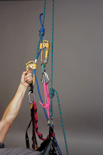 "Use the ""slingshot"" technique to quickly and easily climb doubled rappel ropes that are rigged through metal hardware at the anchors. Pulling down on the jumar side of the rope as shown lifts up on the opposite side of the rope and voila, up you go. In most cases, at some point, you'll have to pass the knot joining the two ropes."