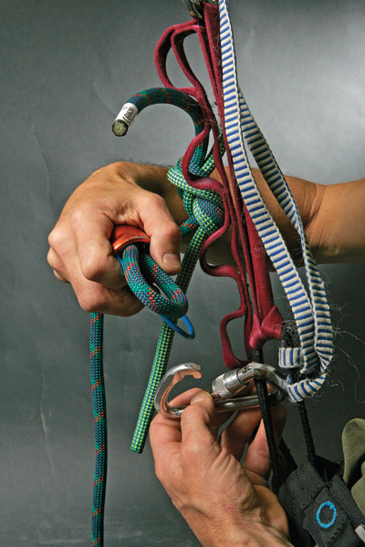 <strong>3.</strong> REMOVE/REINSTALL RAPPEL DEVICE. The rope running through your rappel device should be slack, with all your weight on the bottom ascender, which is backed up by the top ascender. Remove your rappel device from the rope and reinstall it on the rope immediately below the knot.