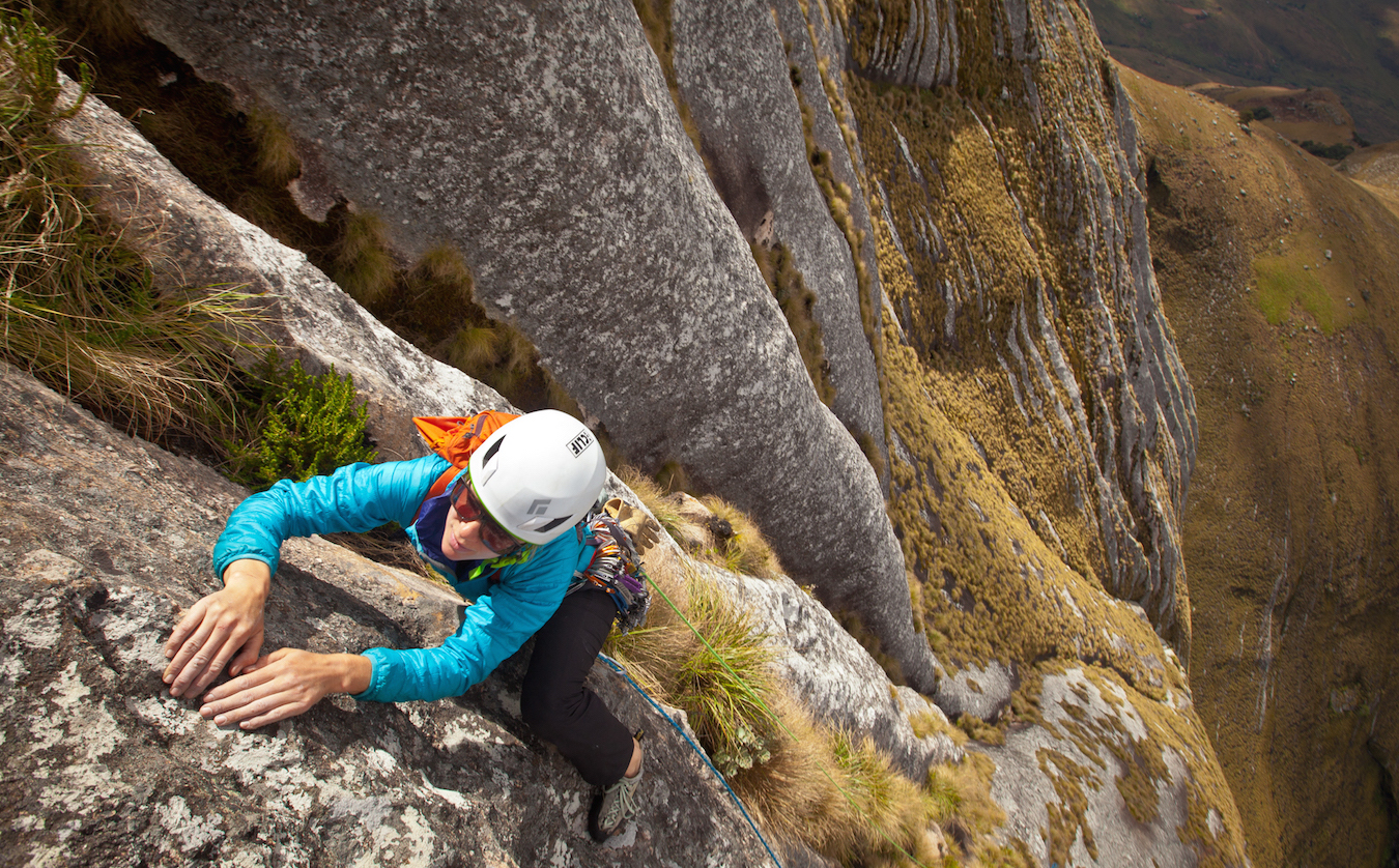 Kate Rutherford leaving the (in)security of the grass hummocks for the unknown slab on one of the crux pitches of <em>Majka and Kate's Science Project</em> (5.10-, IV, 12 pitches).&#8221;> Photo by <a target=