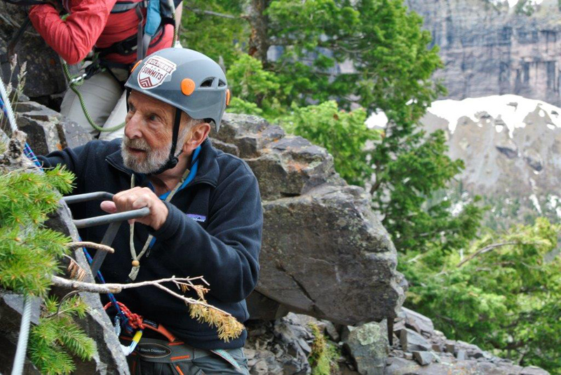 Tom Hornbein climbs a via ferrata above Telluride during the 35th Mountainfilm festival. Photo by Charley Mace.