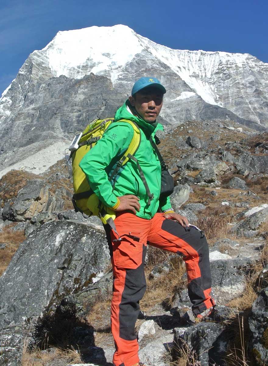 Mingma Gyalje Sherpa stands below Mt. Chobuje's (6,685m) unclimbed West Face, Nepal. Photo courtesy of Mingma Sherpa.