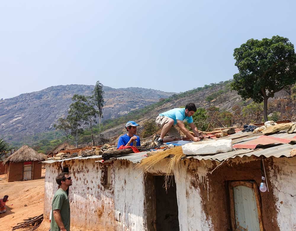 Honnold installs solar panels on the roof of a hut in Angola with Andrew Kent from BBOXX, Honnold Foundation executing partner in the Angola Solar project, while Ted Hesser looks on