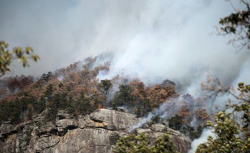 A wildfire raging at Rumbling Bald Mountain, Chimney Rock State Park. It is only one of many conflagrations in western North Carolina. Photo: Maddy Jones/Asheville Citizen-Times.